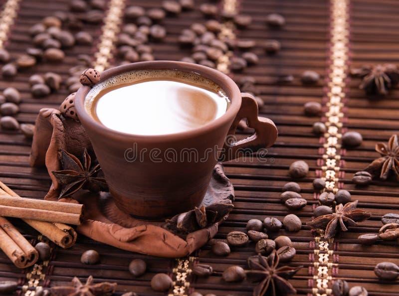 磨咖啡器和热的咖啡在木桌上的 免版税库存照片