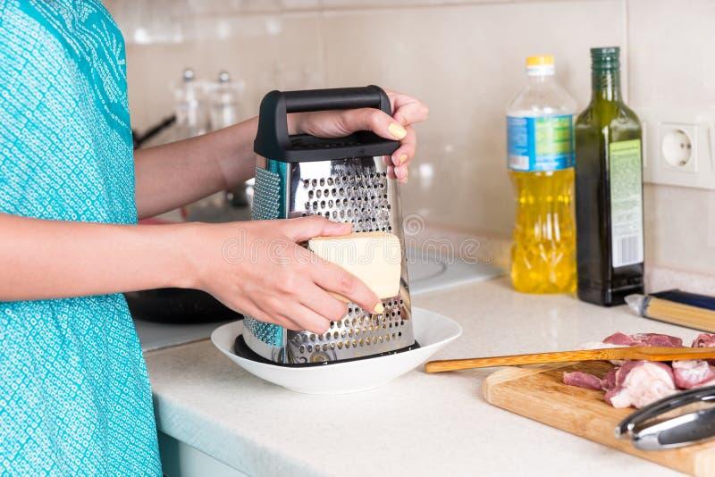 磨碎乳酪的楔子食谱的妇女 图库摄影