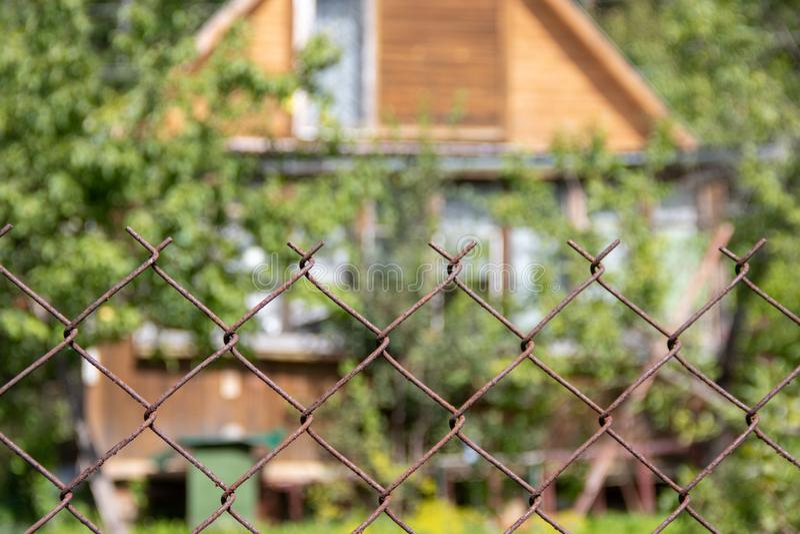 磨碎在被弄脏的村庄背景的篱芭  免版税库存图片
