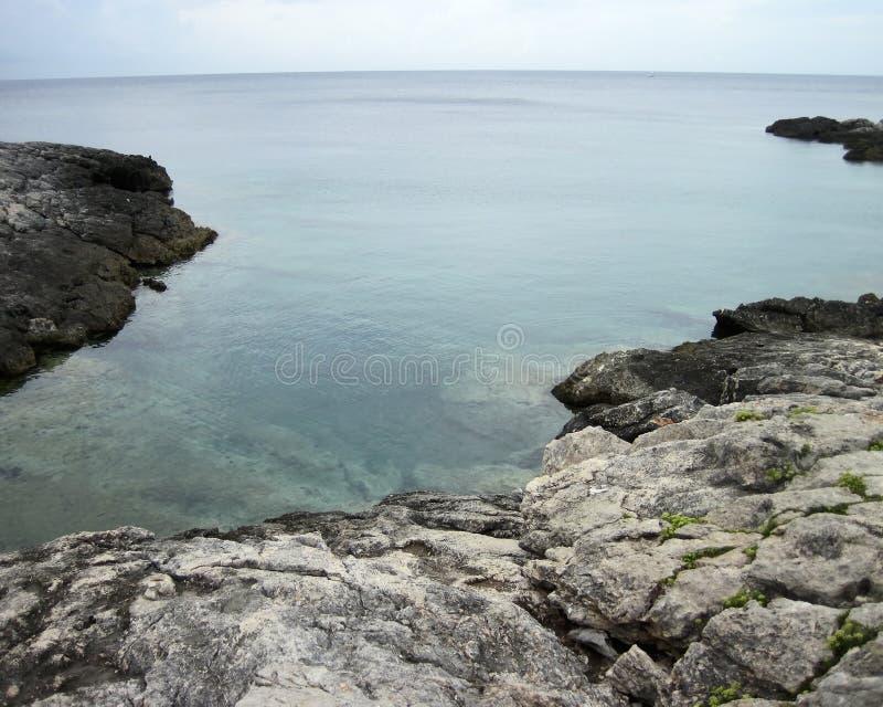 礁石和云彩在水边缘在海岛命名了圣多米诺 Tremiti 库存照片