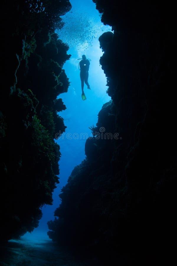 礁石空隙的轻潜水员 免版税库存照片