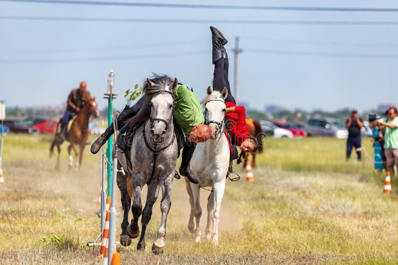 示范哥萨克人马术运动棍打与杂技元素和把戏 免版税库存图片