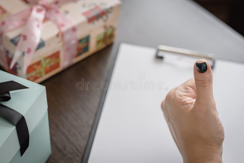 礼品包装材料的概念在假日 显示赞许作为认同的标志,在桌上的礼物的女性手与弓 库存照片