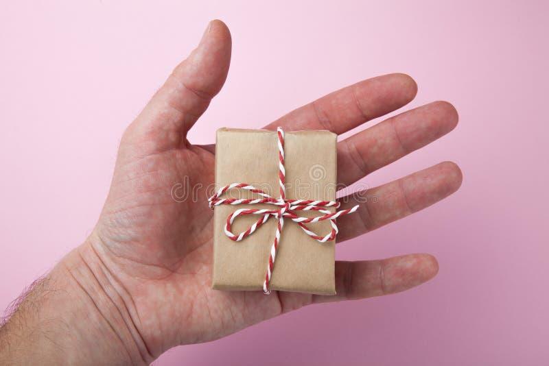 礼品特写镜头 一件美丽的礼物在人的手上 桃红色背景 免版税库存照片