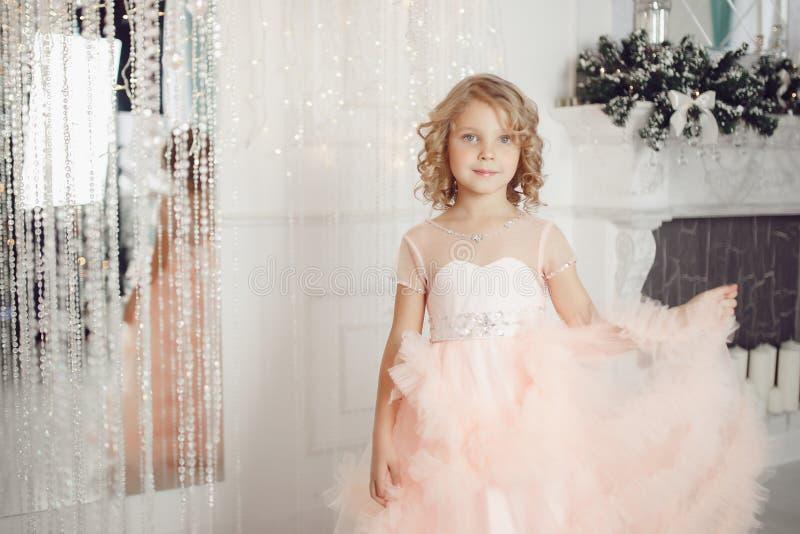 礼服云彩藏品吊边白色壁炉的美丽的女婴 库存照片