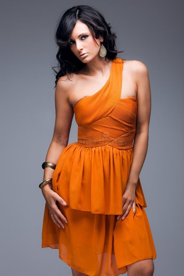 礼服典雅的橙色妇女 库存照片