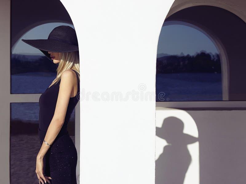 黑礼服和帽子的女孩 免版税库存照片