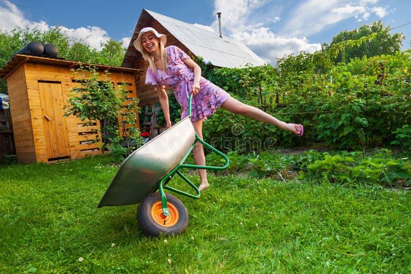 礼服和帽子的年轻美女金发碧眼的女人,获得乐趣在拿着在她的手上在草坪的庭院一个绿色推车有草的 免版税图库摄影