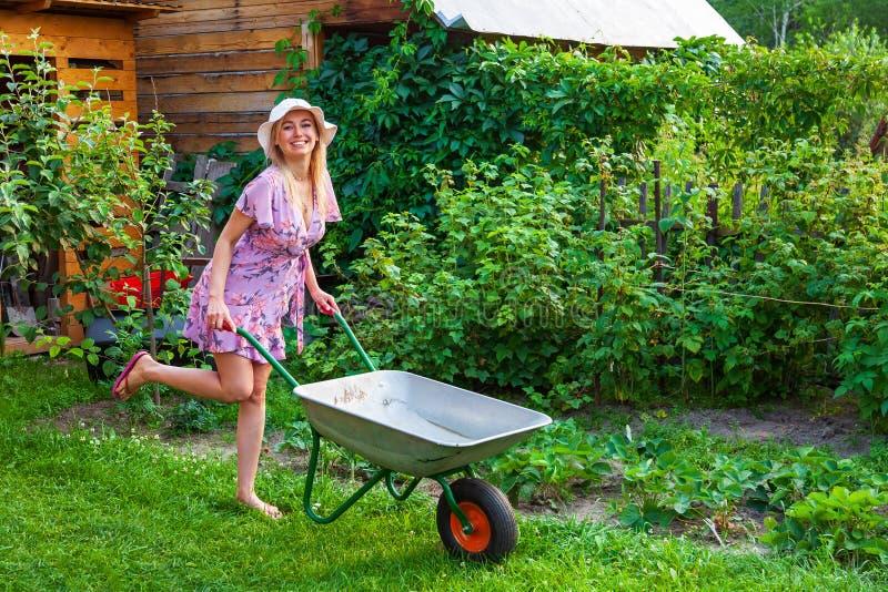 礼服和帽子的年轻美女金发碧眼的女人,获得乐趣在拿着在她的手上在草坪的庭院一个绿色推车有草的 免版税库存图片