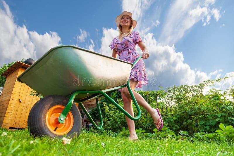 礼服和帽子的年轻美女金发碧眼的女人,获得乐趣在拿着在她的手上在草坪的庭院一个绿色推车有草的 库存照片