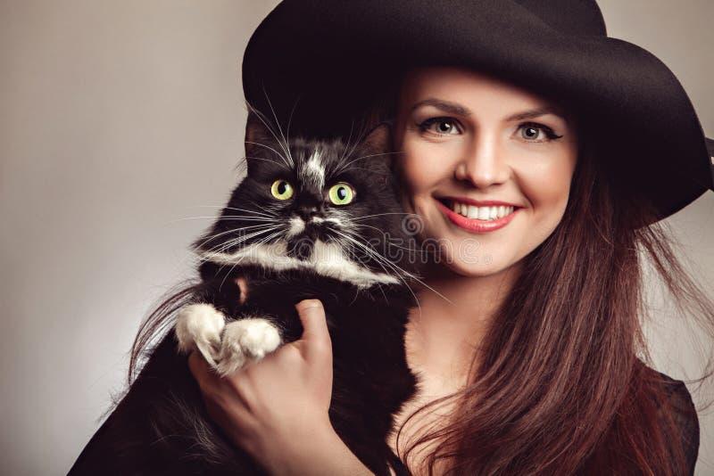 黑礼服和帽子的美丽的妇女有猫的 免版税库存照片