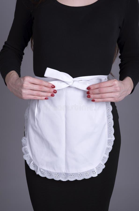黑礼服和白色围裙的女服务员 库存照片