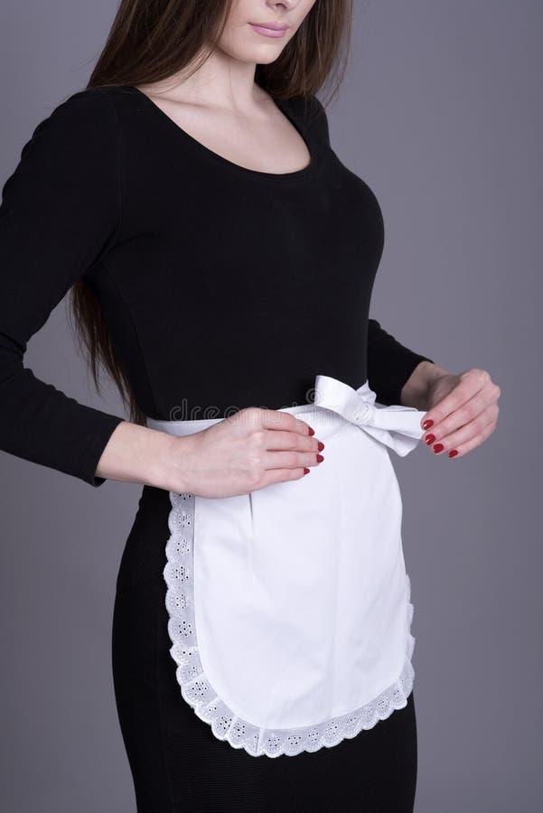 黑礼服和白色围裙的女服务员 免版税库存图片