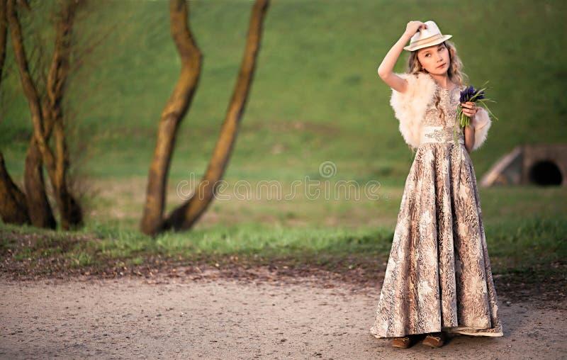 礼服和皮大衣的女孩在太阳光芒  库存图片