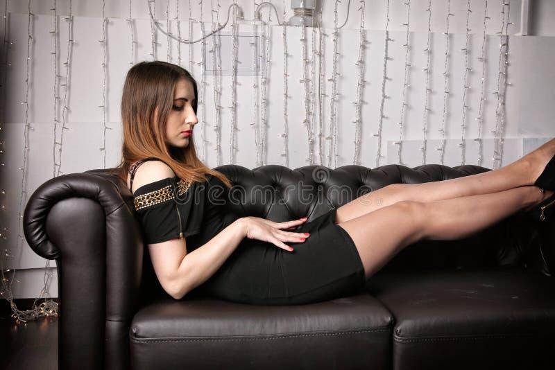 礼服和脚跟的少妇坐一个黑皮革长沙发 免版税库存照片