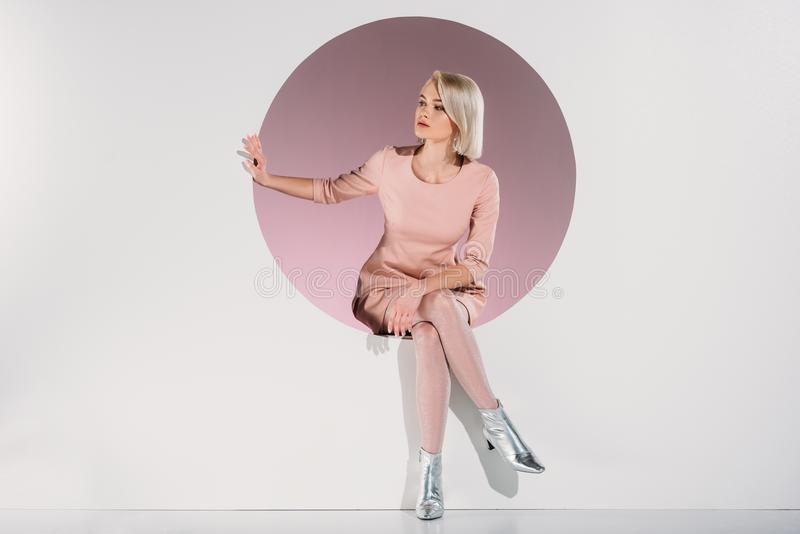 礼服和银的美丽的时髦的白肤金发的女孩穿上鞋子坐在孔和看  免版税库存照片