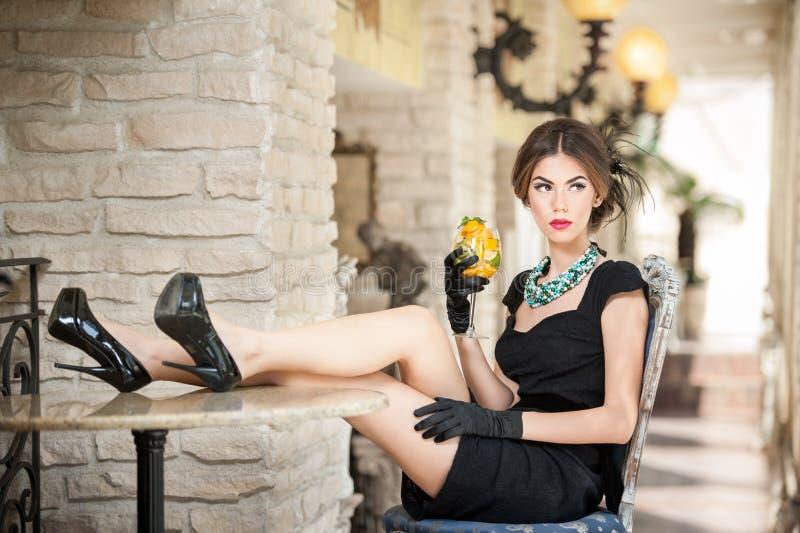 黑礼服坐的时兴的可爱的少妇舒适在餐馆 深色放松与在桌上的腿 免版税图库摄影