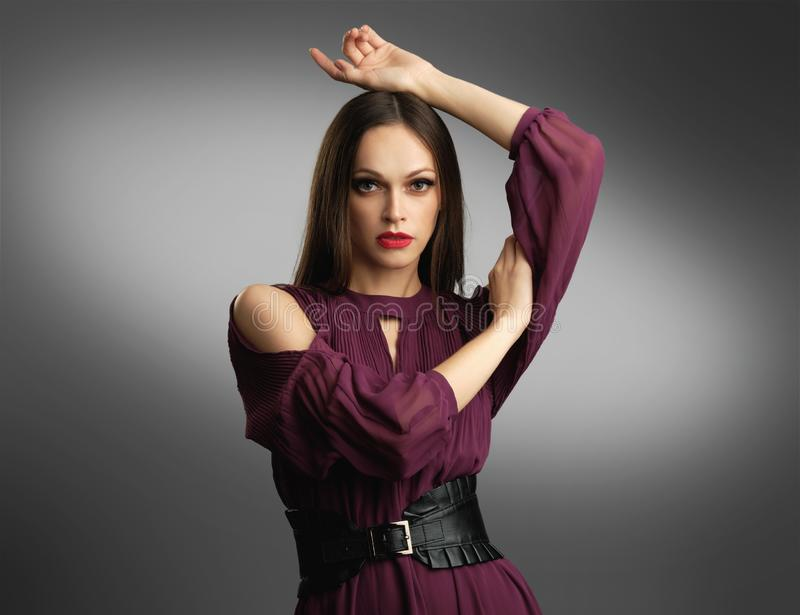 礼服摆在的时髦的女人 免版税库存照片