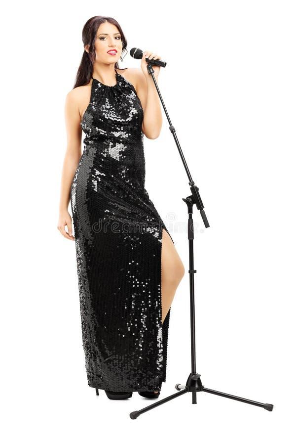 黑礼服摆在的年轻女歌手 免版税库存图片