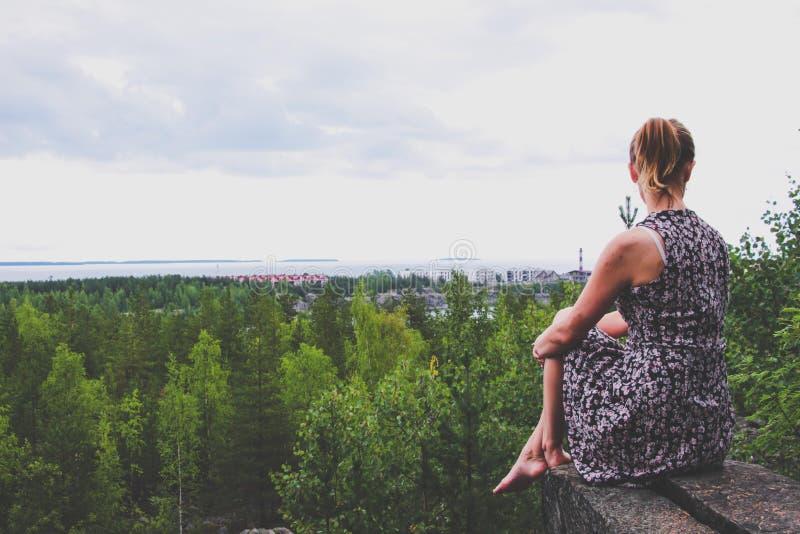 礼服的一个女孩坐在森林上的一个岩石壁架,位于一个巨大的湖的岸 免版税库存照片