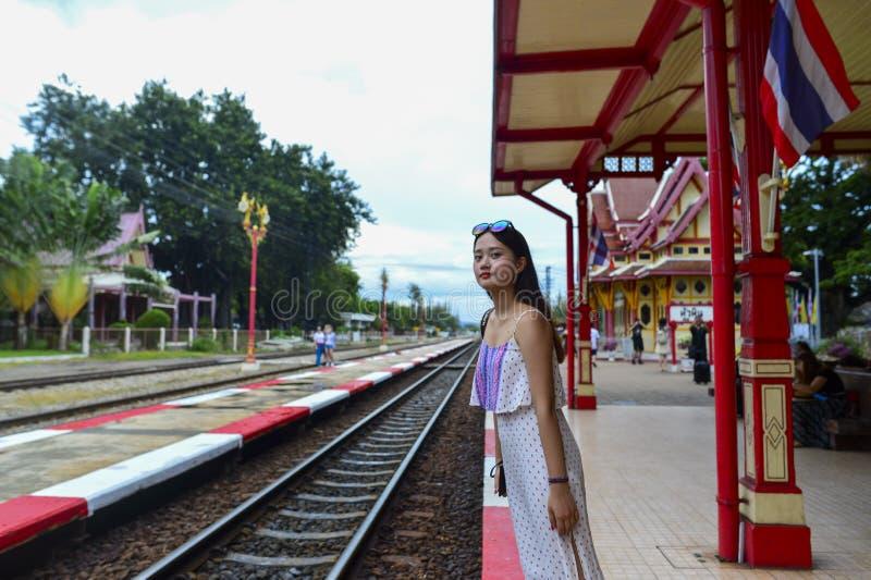 礼服的一个女孩等待火车在华欣火车站 库存照片