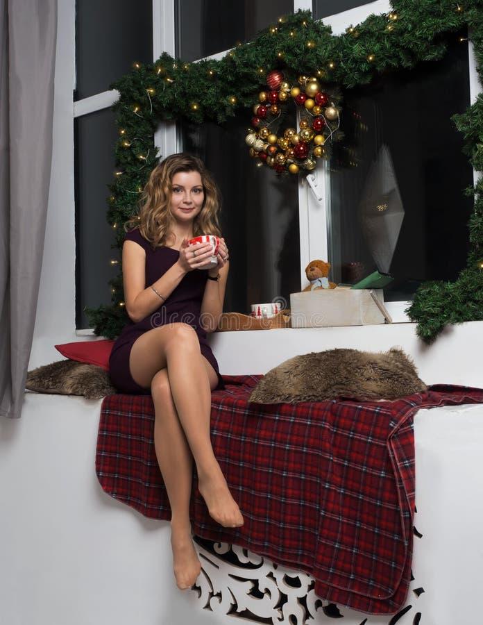 礼服的一个美丽的女孩在新年` s窗口附近坐并且喝一份热的饮料 圣诞树的分支的装饰, 免版税图库摄影