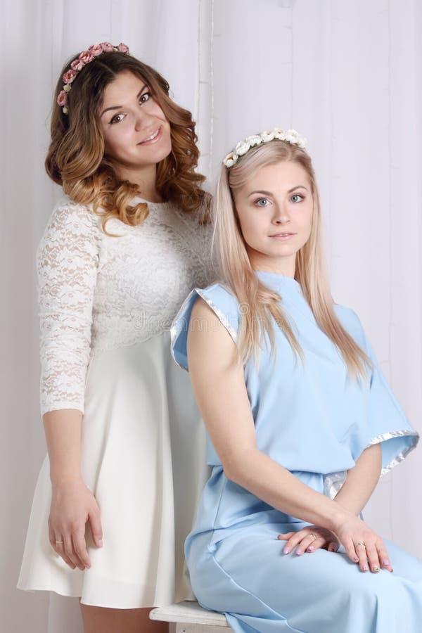 干了女儿和她的两个美丽女同学_礼服的两个美丽的女孩有在头发的花的