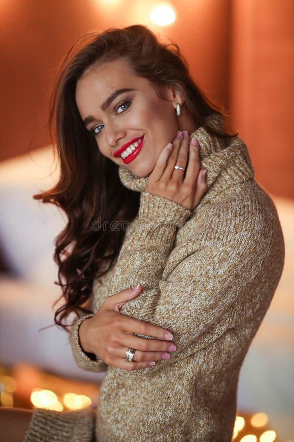 礼服的俏丽的时髦的女孩有坐在沙发的发型和构成的 时尚魅力画象 库存照片