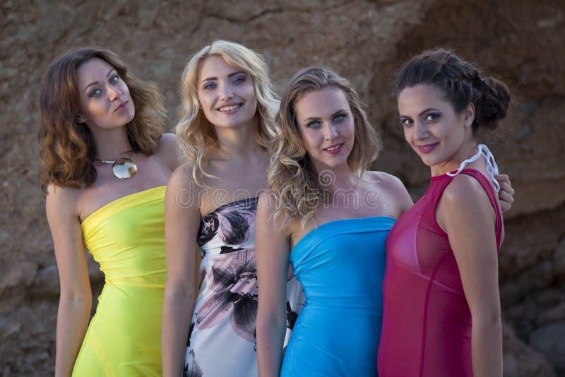 礼服的四个愉快的女孩 免版税库存照片