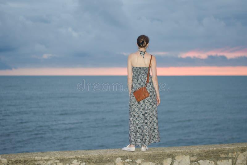 礼服的女孩在一个码头在海和黑暗的天空的背景中站立在日落以后 免版税图库摄影
