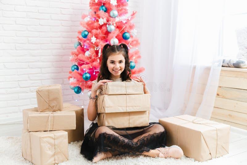 礼服的女孩在家坐地板在圣诞节桃红色树附近并且拿着有礼物的箱子 免版税库存图片