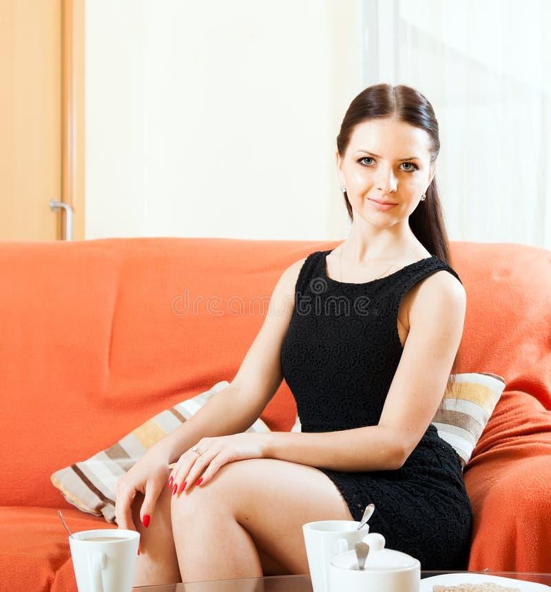 黑礼服的女孩坐沙发 免版税库存照片