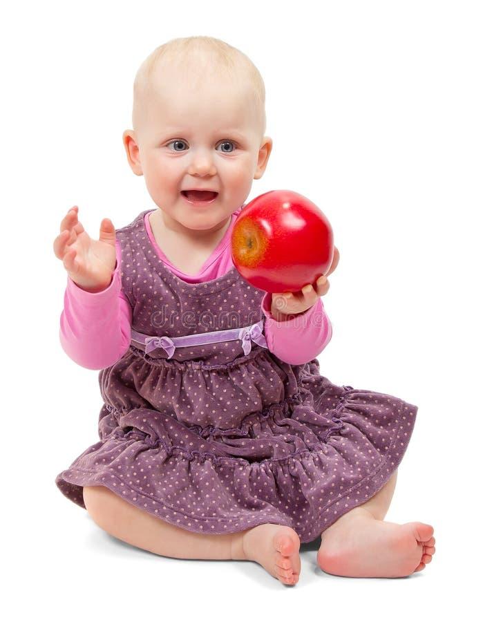 礼服的女孩坐用苹果 免版税库存照片