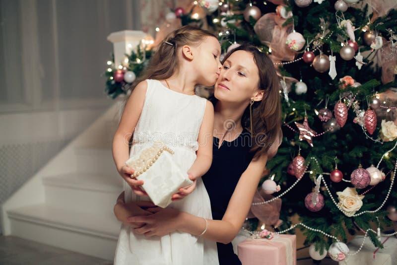 礼服的女孩有在圣诞树附近的妈妈的,拿着礼物 免版税库存照片