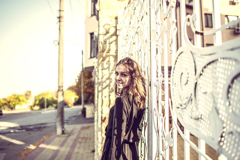 黑礼服的女孩,秋天时间在城市 免版税库存照片