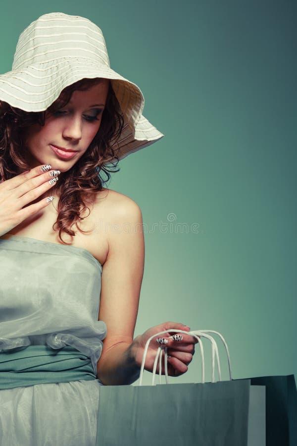 礼服的妇女和帽子拿着购物袋 免版税图库摄影