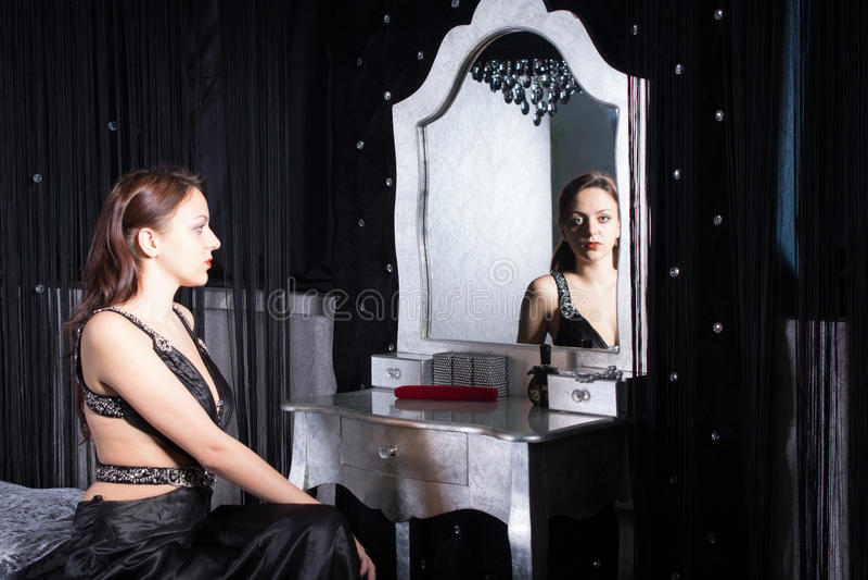 黑礼服的安装的妇女在前面镜子 免版税图库摄影