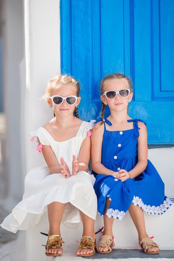 礼服的小愉快的女孩在典型的希腊传统村庄街道在米科诺斯岛海岛上的,在希腊 免版税库存图片