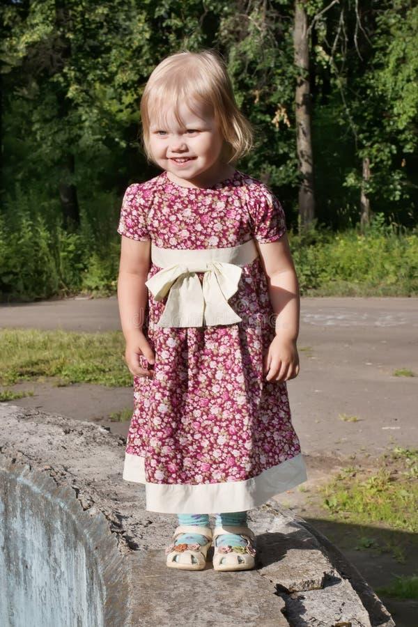 礼服的小白肤金发的女孩在公园站立晴天a 库存图片