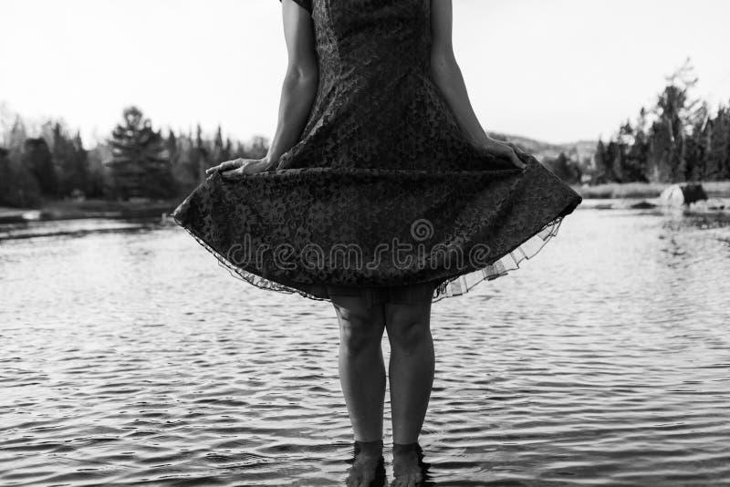 礼服的年轻女人摆在以逗人喜爱的方式,当站立在水中时 免版税库存图片