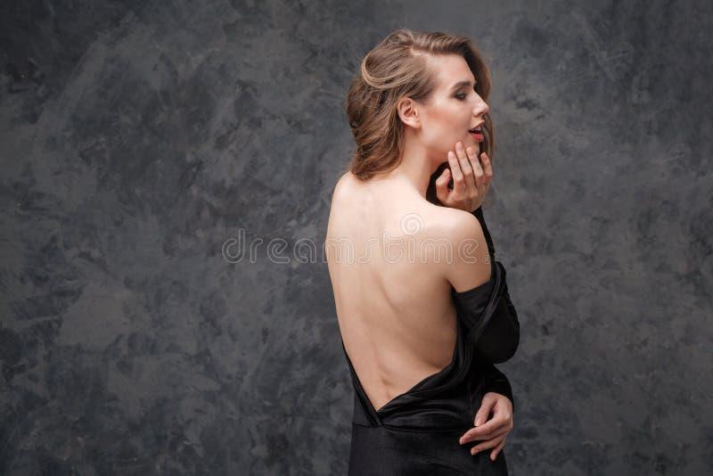 黑礼服的引诱的迷人的少妇有的开背部 库存图片