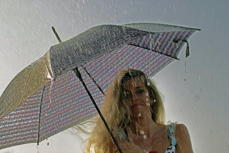 礼服的微笑的白肤金发的女孩有伞的,多雨天气 库存照片