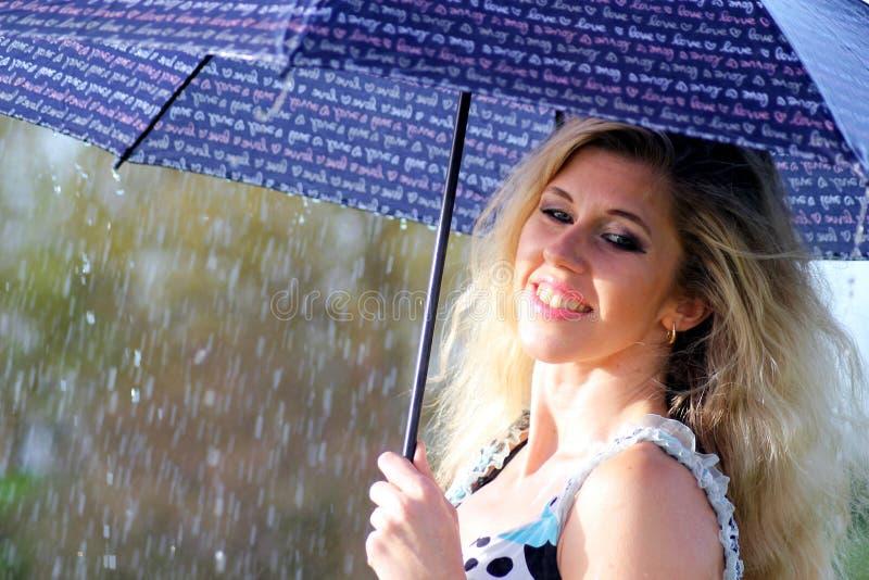 礼服的微笑的白肤金发的女孩有伞的,多雨天气 免版税库存照片