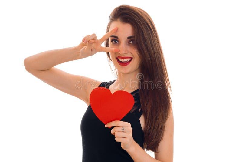 黑礼服的快乐的深色的女孩有好的组成庆祝与红色心脏的情人节在她的被隔绝的手上  库存照片