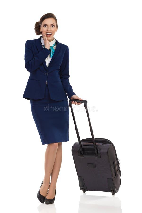 礼服的惊奇的妇女站立与客舱袋子 免版税图库摄影