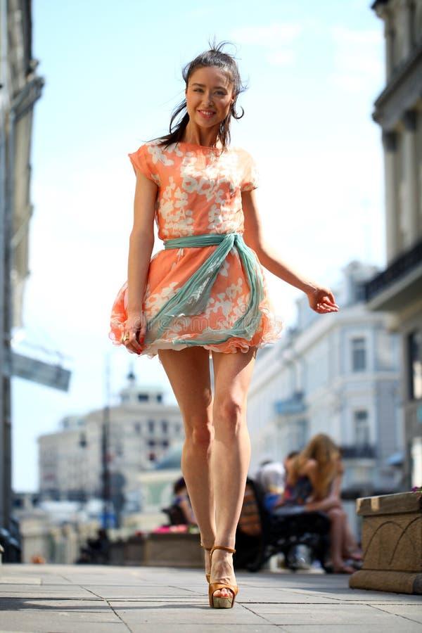 礼服的愉快的妇女在街道上 库存图片