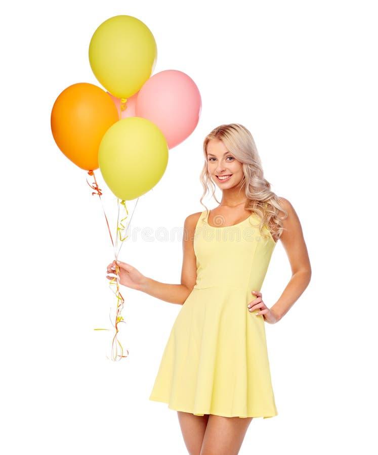 礼服的愉快的妇女有氦气气球的 免版税库存图片