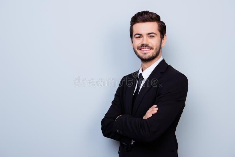 礼服的愉快的微笑的年轻英俊的人与横渡的韩 库存照片
