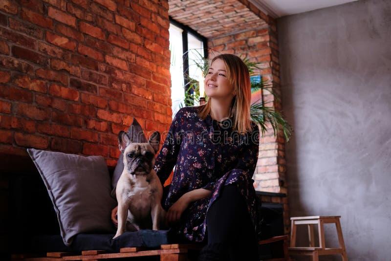 礼服的愉快的白肤金发的妇女与她逗人喜爱的哈巴狗坐一个手工制造沙发在有顶楼内部的屋子里 免版税库存图片