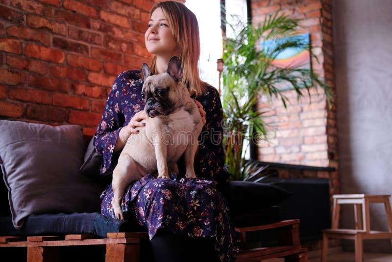 礼服的愉快的白肤金发的妇女与她逗人喜爱的哈巴狗坐一个手工制造沙发在有顶楼内部的屋子里 库存图片